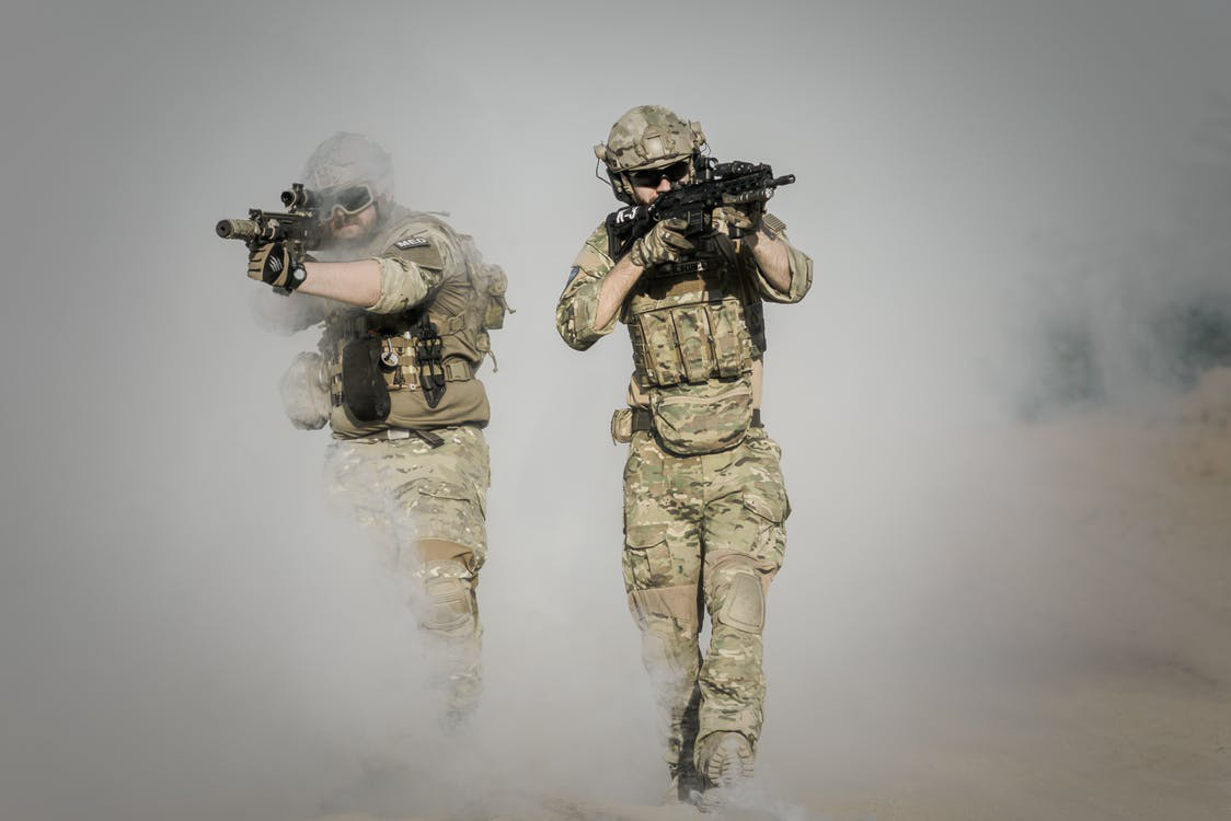 Two solders wearing tactical vests walking through the smoke with rifles in their hands